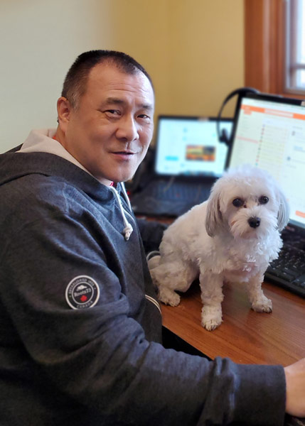 Kelvin Lee sitting at home office with dog on desk